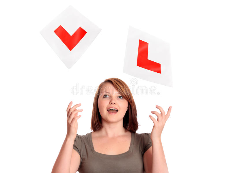Pretty teenage girl passing her driving test. Pretty teenage girl throwing away her L-plates after passing her driving test stock image
