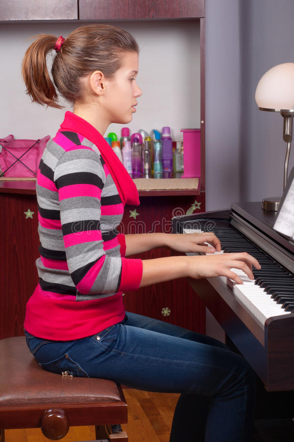 Pretty teenage girl playing on piano stock images
