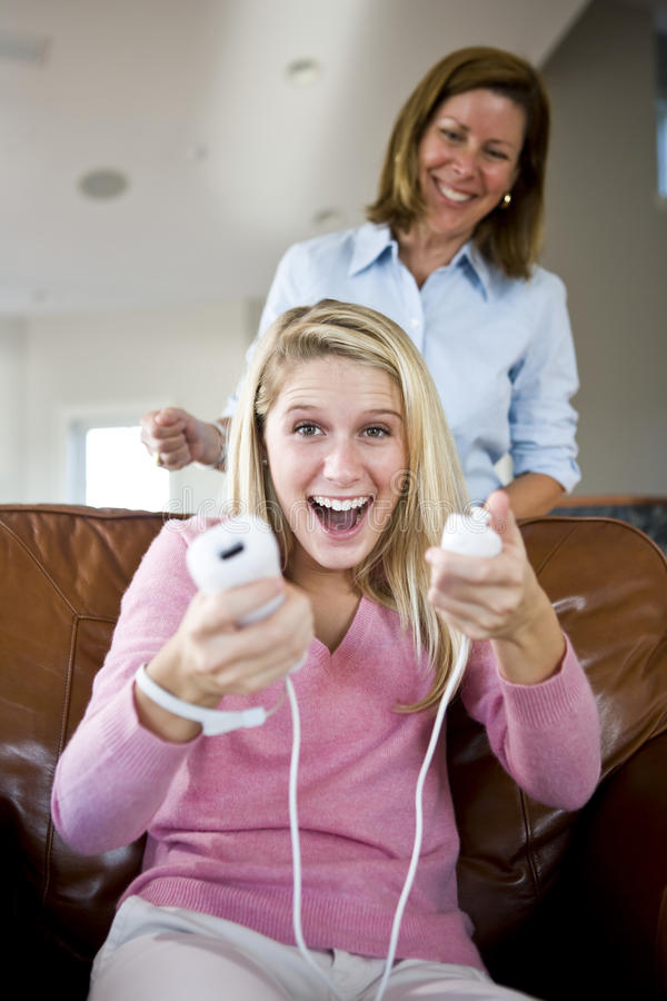 Pretty teenage girl playing video games at home royalty free stock images