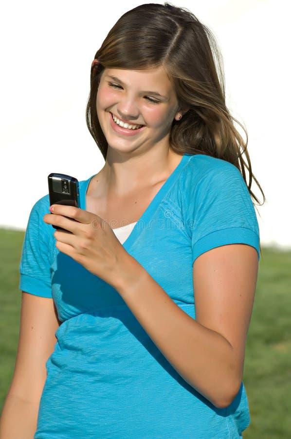 Pretty teenage girl reading text message stock photos