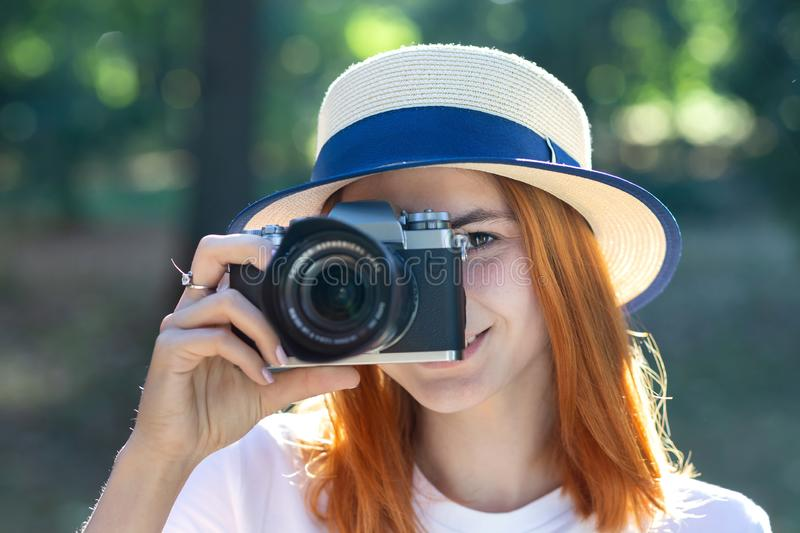 Pretty teenage girl with red hair taking picture with photo camera in summer park royalty free stock photos