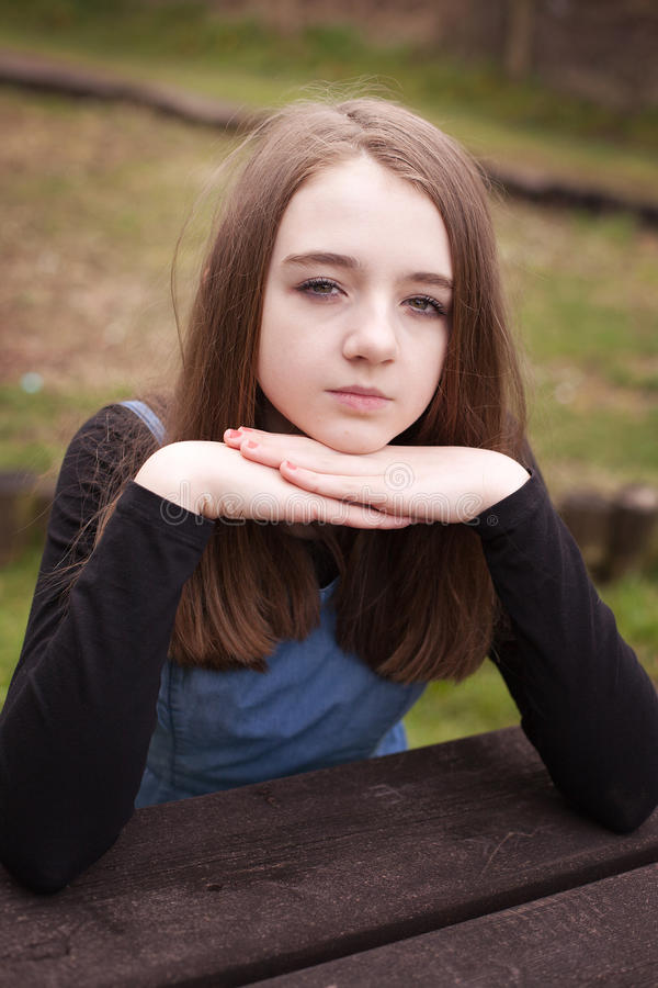 Pretty teenage girl sitting outdoors at a picnic table royalty free stock photography