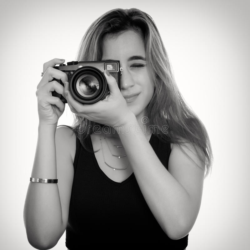 Pretty teenage girl taking pictures with a professional camera. Black and white portrait of a pretty teenage girl taking pictures with a professional camera - on stock photos