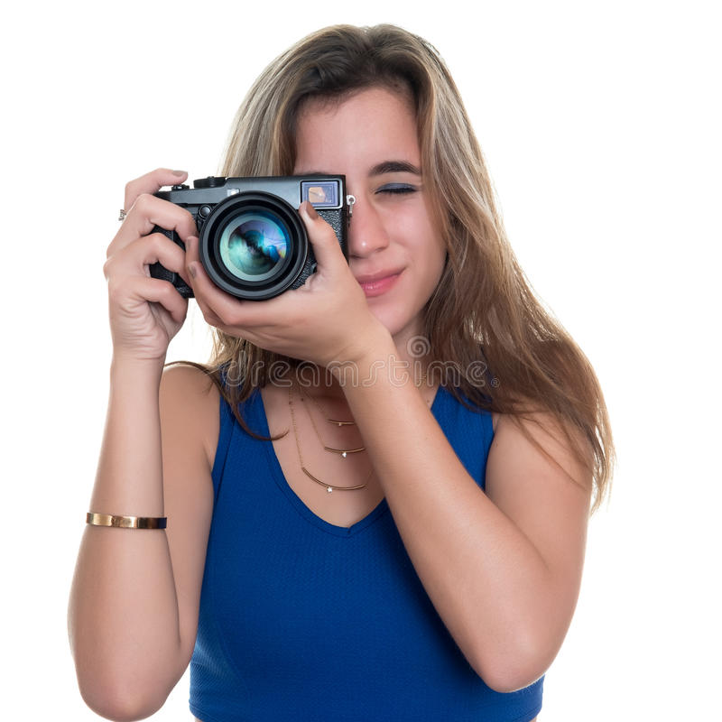 Pretty teenage girl taking pictures with a professional camera. Isolated on a white background stock photos