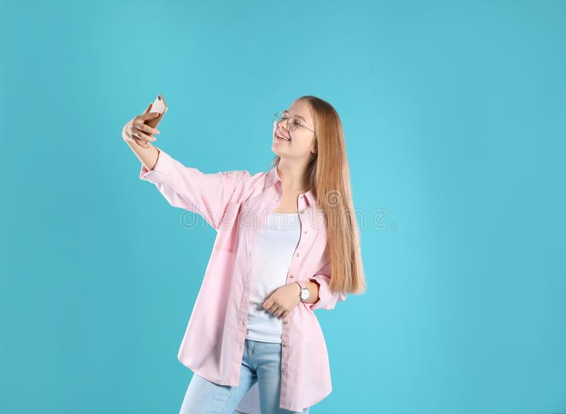 Pretty teenage girl taking selfie on background stock images