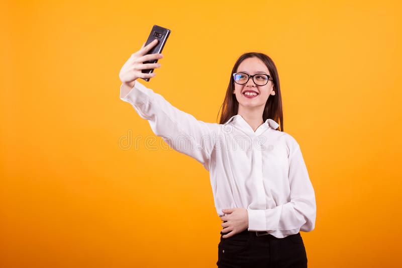 Pretty teenage girl taking a selfie and smiling to the camera over yellow background stock images