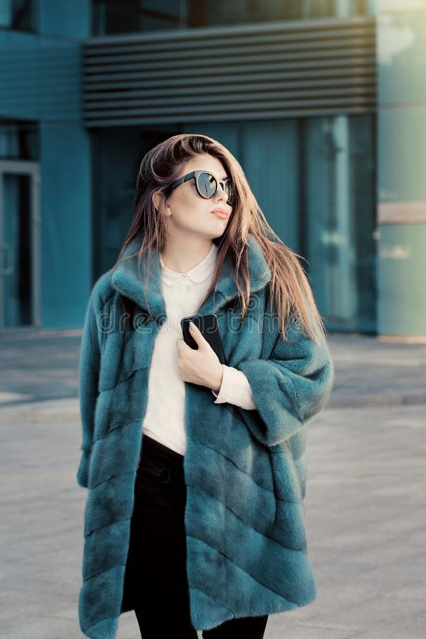 Pretty teenage girl in a bright colorful natural fur coat and sunglasses royalty free stock images