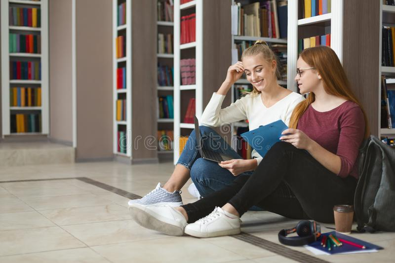 Pretty teenage girlfriends studying on floor in library royalty free stock photo