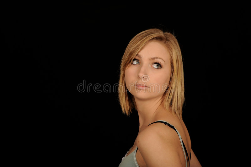 Pretty Teenager. A portrait of a pretty teenage girl, on black studio background stock photography