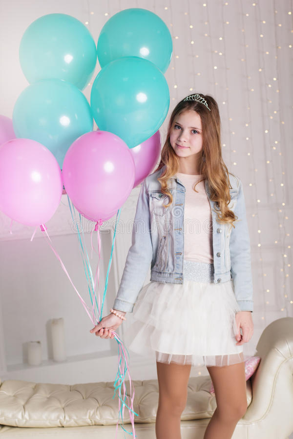 Pretty teenager girl with many blue and pink balloons stock image