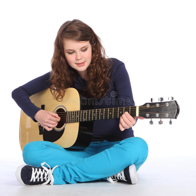 Pretty teenager girl music on acoustic guitar. Happy concentration from pretty teenager girl sitting on floor playing music on acoustic guitar. She is wearing royalty free stock photos