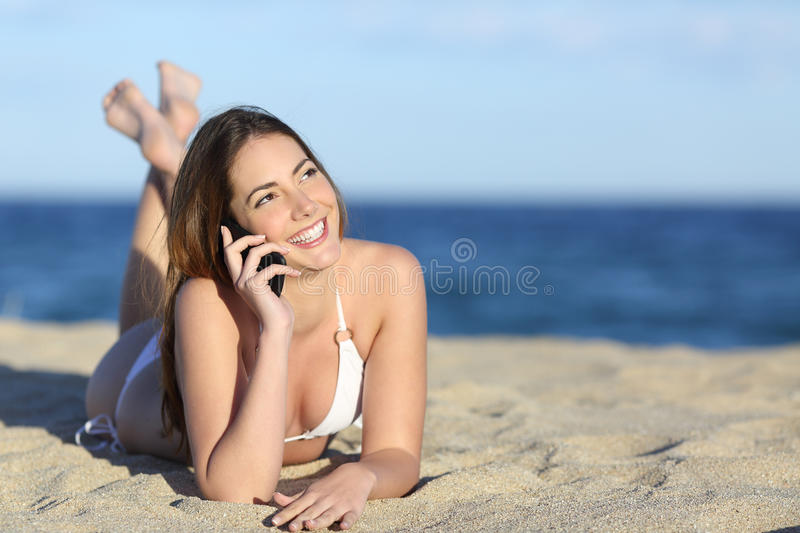 Pretty teenager girl on the phone lying on the beach. With the horizon in the background royalty free stock image