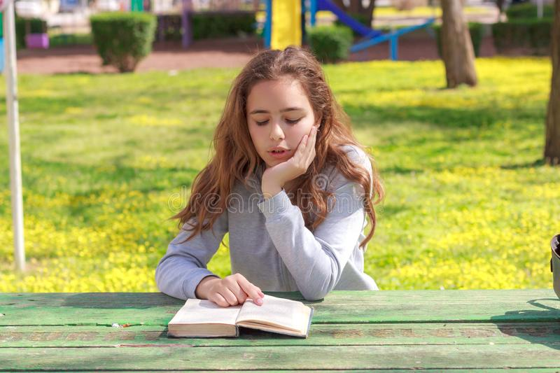 Pretty teenager girl reading a book and studying homework at the summer park stock photo
