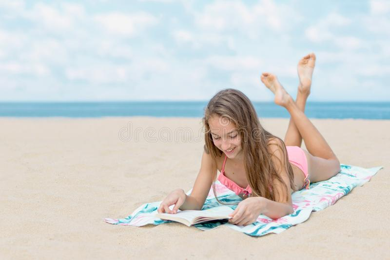 Pretty teenager girl reading book and sunbathing on the beach on the hot summer day with the sea and horizon in the background royalty free stock photos
