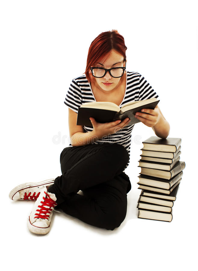 Pretty teenager girl sit on floor and reading book. On white background royalty free stock photos