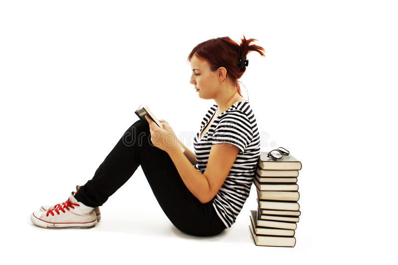 Pretty teenager girl sit on floor and reading book. On white background stock images
