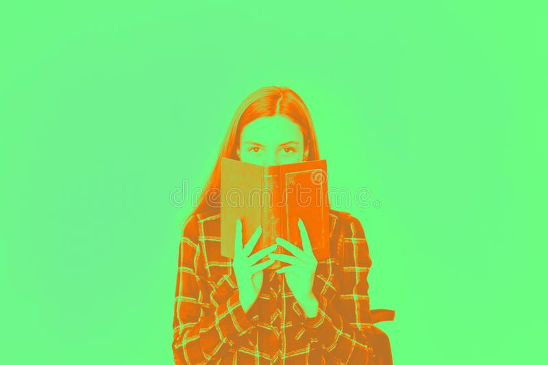 Pretty teenager girl student with book in her hands hiding face with copy space royalty free stock image