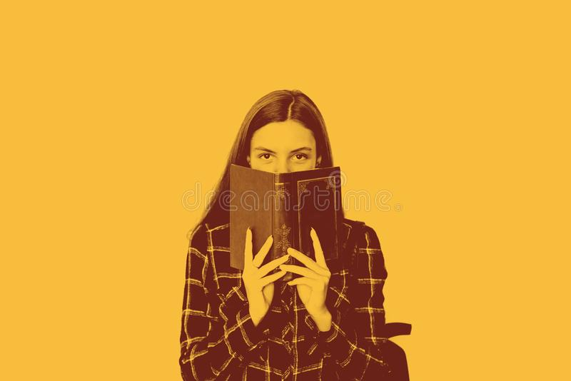 Pretty teenager girl student with book in her hands hiding face with copy space stock photos