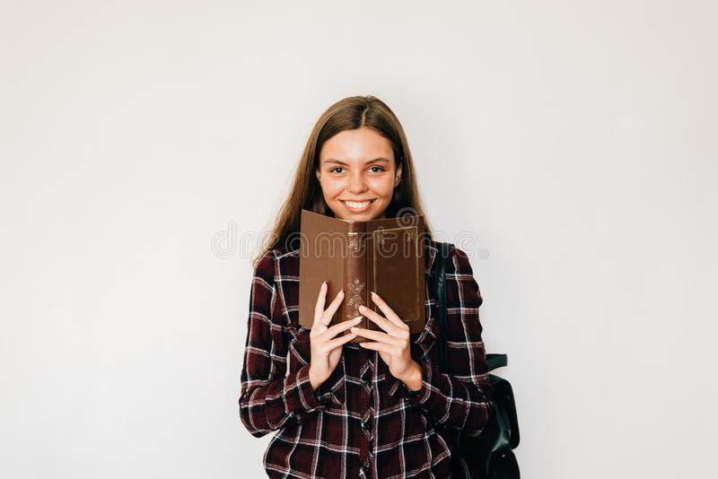 Pretty teenager girl student with book in her hands hiding face with copy space and white background smiling royalty free stock photography