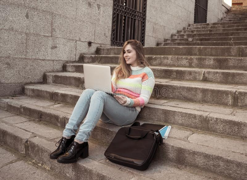 Pretty teenager student girl on laptop chatting online talking with blog followers in social media. Attractive trendy teen student girl or young college woman royalty free stock images