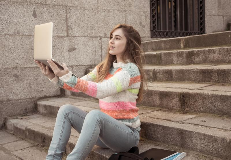Pretty teenager student girl on laptop chatting online talking with blog followers in social media. Attractive trendy teen student girl or young college woman stock photography