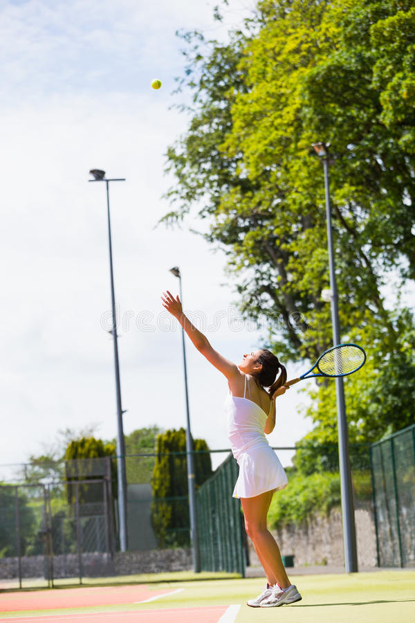 Pretty tennis player about to serve. On a sunny day royalty free stock images