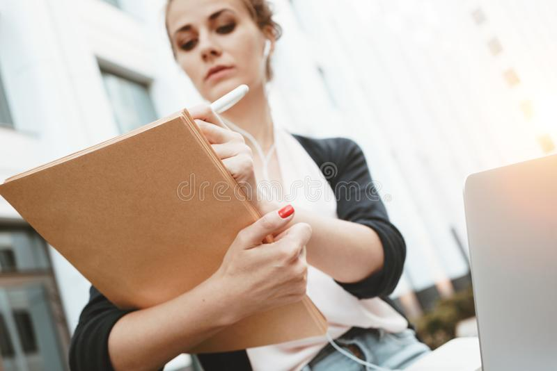 Pretty thoughtful female student sits in urban street near university and looking for information on the Internet. Young woman pro. Fessor prepares for lecture royalty free stock photo