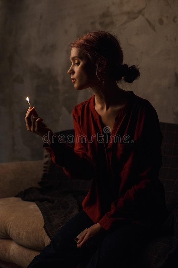 Pretty thoughtful girl in red shirt sits in dark room, lights up burning matchstick and holds matchbox in her hand royalty free stock image