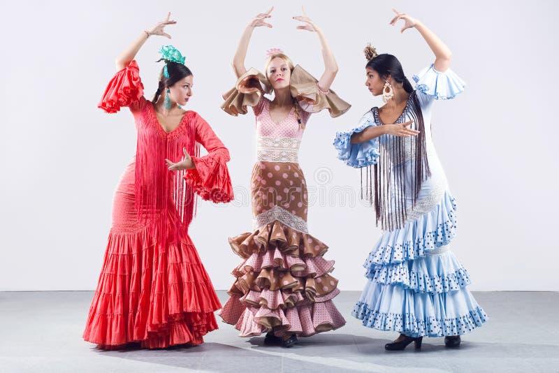 Pretty three young flamenco dancer in beautiful dress. stock photos