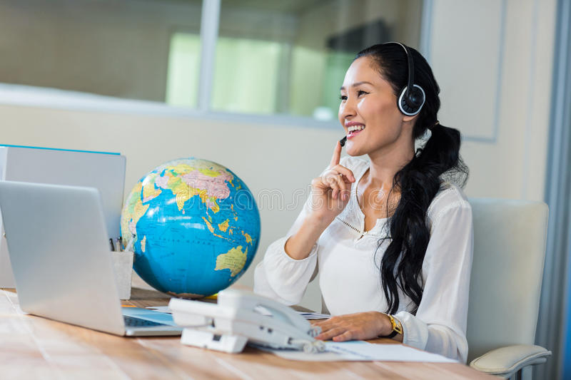 Pretty travel agent speaking to customer. In the office royalty free stock photo