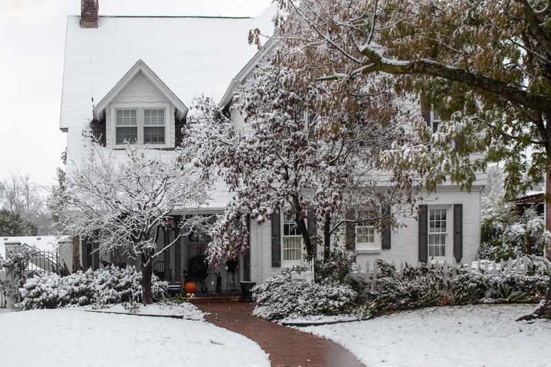 Pretty two story white clapboard house with shutters during a snow storm with sidewalk cleared and snow on the trees.  royalty free stock photo