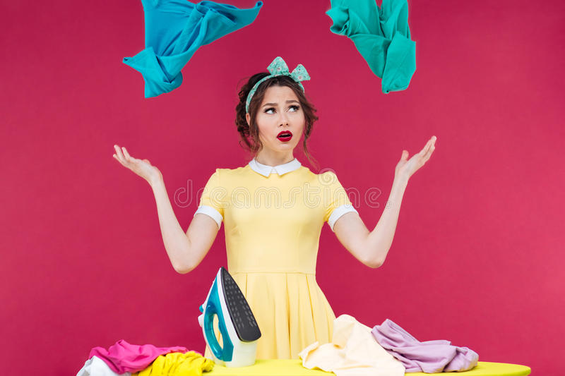 Pretty upset woman with iron throwing clothes in the air. Pretty upset young woman with iron throwing clothes in the air over pink background royalty free stock images