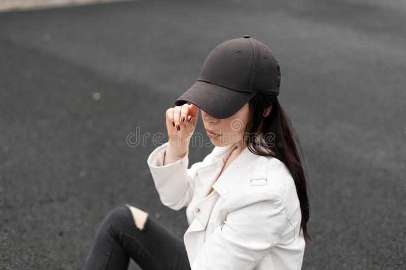 Pretty urban young woman in fashionable black baseball cap in a stylish white leather jacket relaxes and looks down outdoors. royalty free stock photography