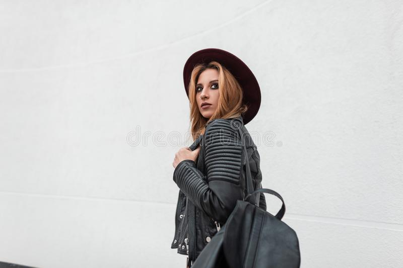 Pretty urban young woman in vintage purple hat in a trendy black leather jacket with a fashionable backpack stands stock photo
