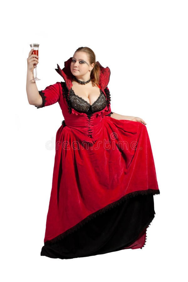 Pretty vampire with glass full of blood stock photography