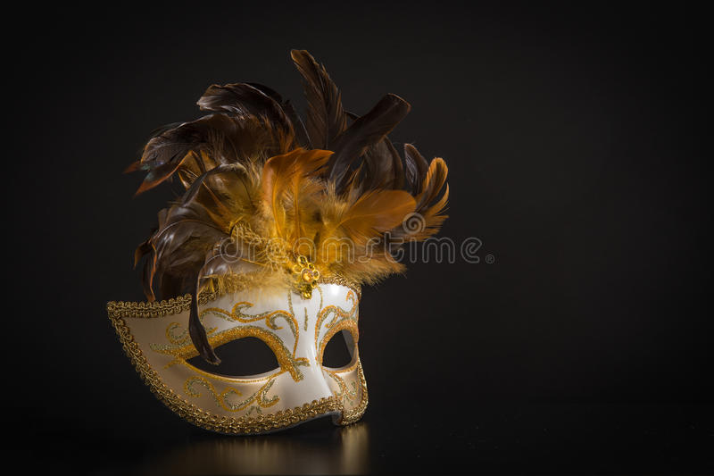 Pretty venician golden carnival mask with feathers on a black background. Pretty venician golden carnival mask with feathers isolated on a mysterious black royalty free stock photo
