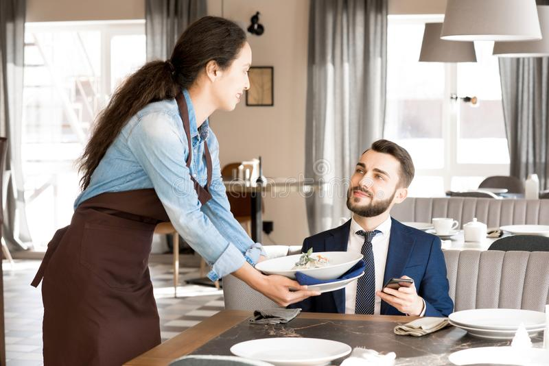 Pretty waitress bringing salad for customer. Content handsome young businessman having lunch in restaurant: bearded men satisfied with restaurant service looking stock photography