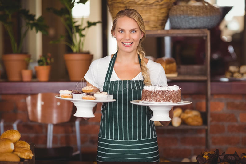 Pretty waitress holding a chocolate cake and cupcakes royalty free stock photos