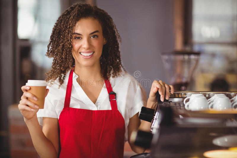 Pretty waitress holding a take-away mug stock photo