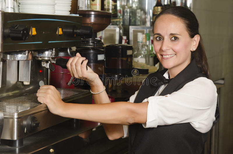 Pretty waitress preparing a coffee stock photography