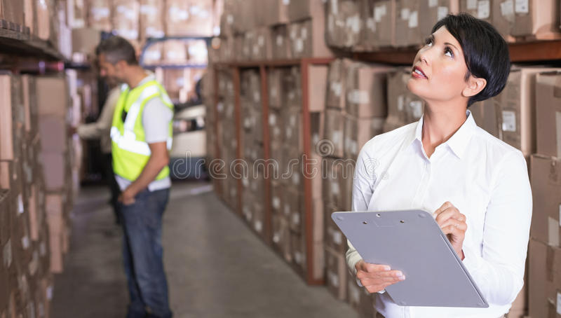Pretty warehouse manager checking inventory. In a large warehouse stock images