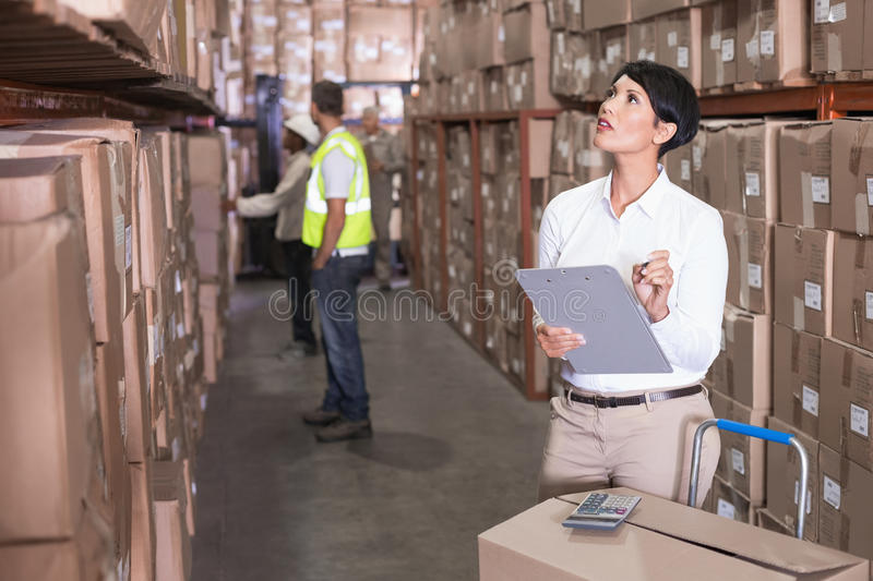Pretty warehouse manager checking inventory. In a large warehouse royalty free stock photo