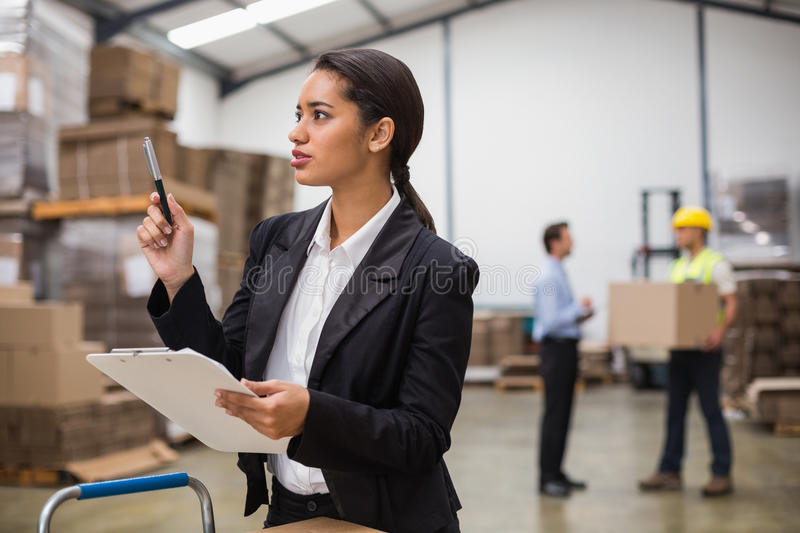 Pretty warehouse manager checking inventory. In a large warehouse stock photo