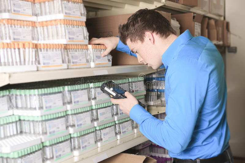 Pretty warehouse manager checking the inventory. A Pretty warehouse manager checking the inventory with a machine royalty free stock photo