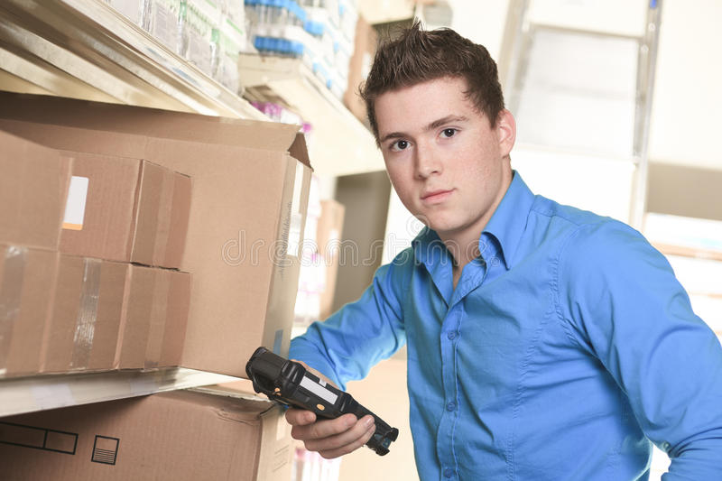 Pretty warehouse manager checking the inventory. A Pretty warehouse manager checking the inventory with a machine stock images