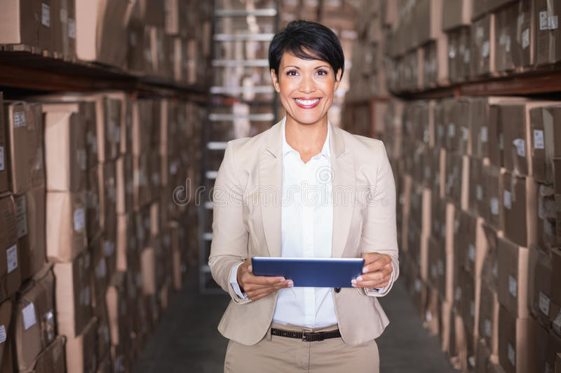 Pretty warehouse manager holding tablet pc. In a large warehouse royalty free stock photo