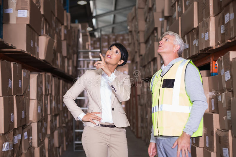 Pretty warehouse manager talking to foreman. In a large warehouse royalty free stock images