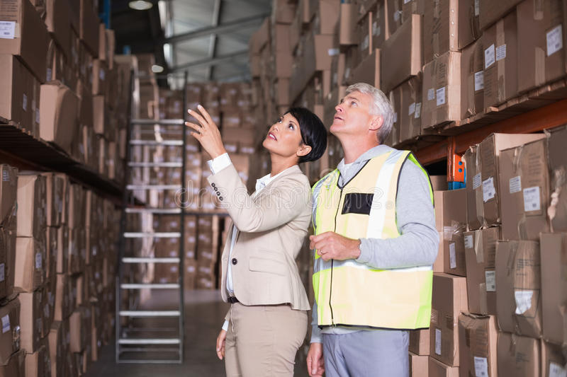 Pretty warehouse manager talking to foreman. In a large warehouse stock image