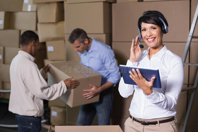 Pretty warehouse manager using tablet during busy period. In a large warehouse stock images