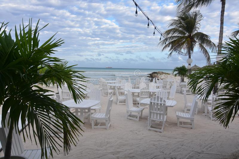Pretty sitting area on eagle beach in Aruba. Pretty white chairs and tables in a sitting area on eagle beach in Aruba stock images